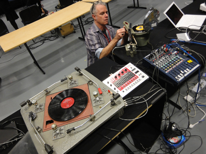 Ian Andrews preparing a medical centrifuge modified to play vinyl records at extremely high speeds, with four-arm turntable constructed by John Jacobs