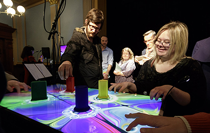 Founding Amplified Elephants member Kathryn Sutherland demonstrates the RESONANCE table for the audience after the concert