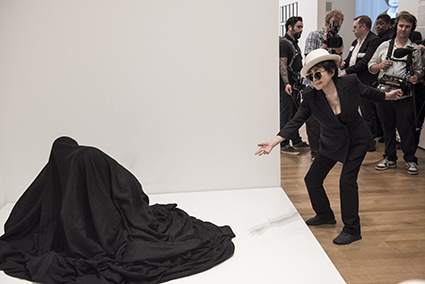 Yoko Ono interacting with people activating Bag Piece (1964), a participatory work in Yoko Ono: One Woman Show, 1960-1971, on view at MoMA, 17 May-7 Sep 2015
